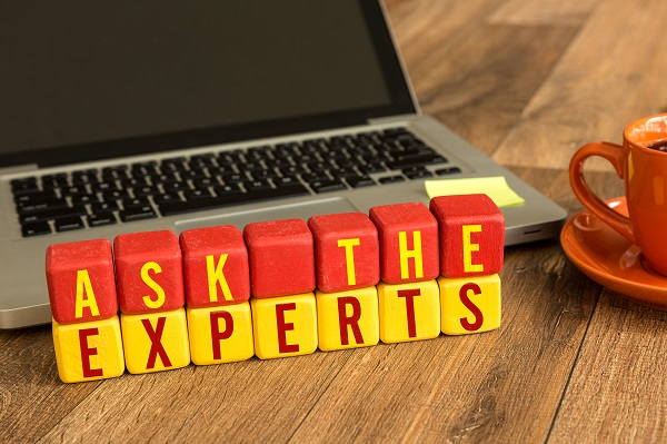 Ask the Experts written on a wooden cube in a office desk
